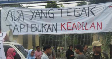 """Banner bertuliskan """"Ada yang tegak tapi bukan keadilan"""" terbentang di samping mobil komando (dok. : Louis King)"""